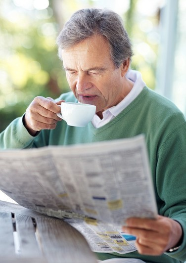 Retired man reading newspaper